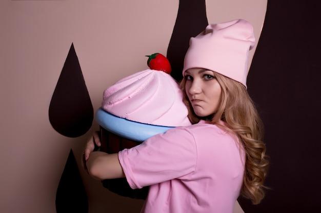 Modèle blonde émotionnelle en t-shirt rose et casquette avec gros cupcake. concept de vacances