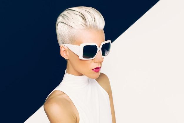 Modèle blonde en lunettes de soleil à la mode avec coupe de cheveux élégante.