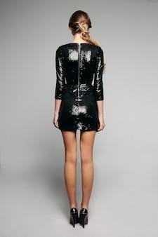 Modèle blonde en robe de cocktail scintillante noire et talons
