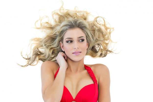 Modèle blonde séduisante, portant un bikini rouge à la recherche