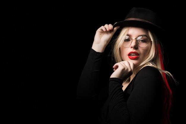 Modèle blonde sexy portant un chemisier noir, un chapeau et des lunettes, posant dans l'ombre