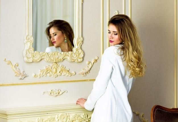 Modèle blonde en suite blanche au miroir