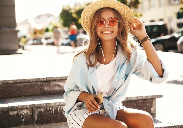 Modèle blonde en vêtements d'été posant dans la rue