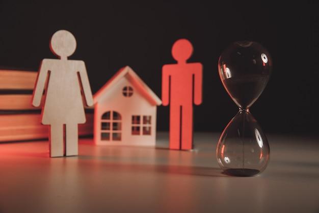 Modèle en bois du concept de divorce de maison de couple et de sablier