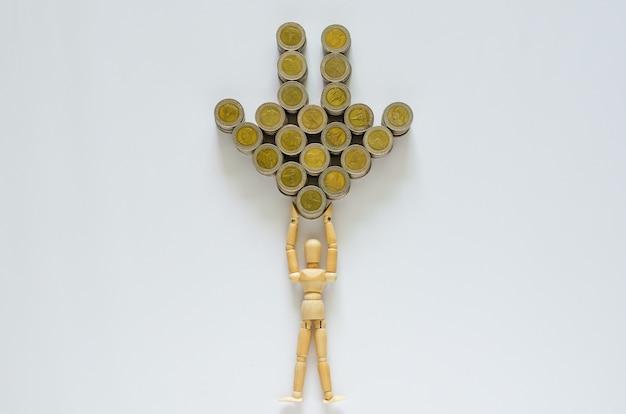 Modèle en bois portant des pièces de monnaie en baht thaïlandais qui se définissent comme une flèche vers le bas.