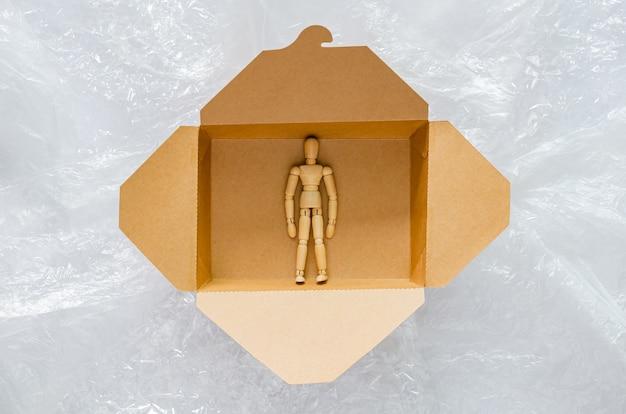 Le modèle en bois reste en sécurité à l'intérieur d'une boîte de nourriture en papier jetable et compostable entourée d'un sac en plastique