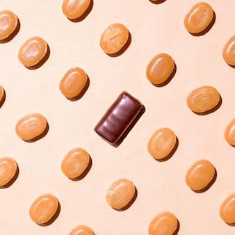 Modèle de bonbons au caramel et au chocolat sur fond beige. vue d'en-haut