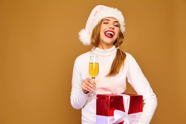 Modèle avec bonnet de noel et grand coffret cadeau buvant du champagne sur mur d'or