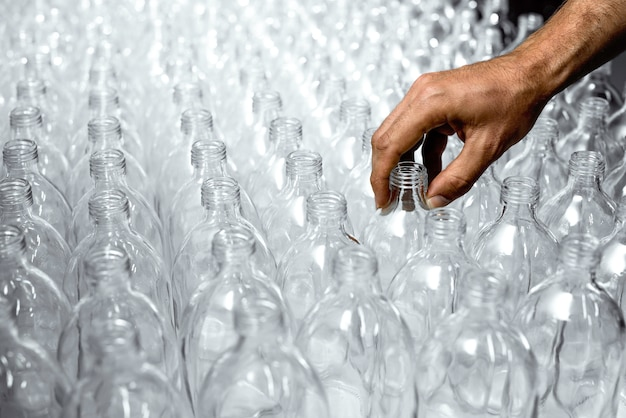 Modèle de bouteilles en verre transparent avec une main dans le processus de fabrication de la boisson saine