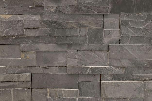 Modèle de brique de surface agrandi au vieux fond de mur de brique en pierre noire