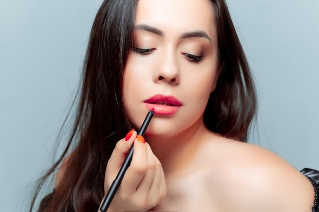 Le modèle brune a appliqué un crayon à lèvres et les peint