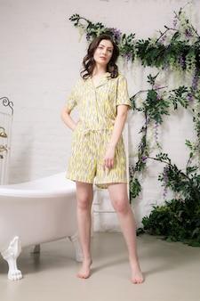 Modèle brune assez caucasienne posant en pyjama jaune dans sa salle de bain confortable blanche.