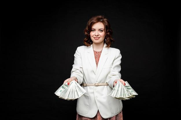 Modèle brune élégante réussie avec de l'argent dans les mains.