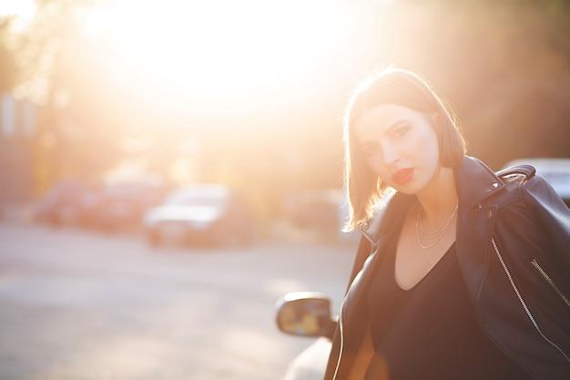Modèle brune glamour avec des lèvres rouges posant près d'une voiture décapotable avec des reflets du soleil. espace pour le texte