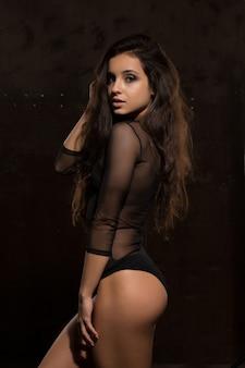 Modèle brune séduisante avec un corps parfait en lingerie sexy posant près d'un mur sombre