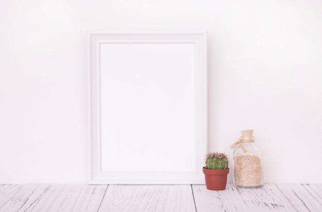 Modèle de cadre blanc rétro table en bois vintage et bouteille de sable en verre cactus