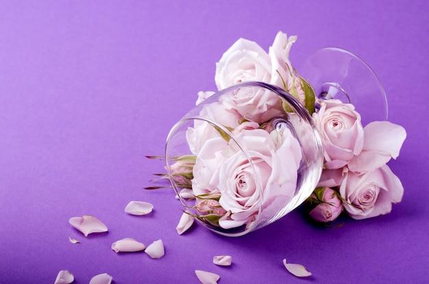 Un modèle de carte postale ou d'invitation avec une belle composition floristique de roses lilas dans le verre.