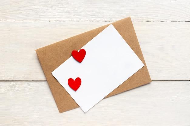 Modèle de carte de voeux avec enveloppe en papier craft et coeurs rouges vifs. conception de texte de carte pour les blogs de médias sociaux.
