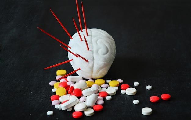 Modèle de cerveau humain avec des aiguilles rouges et des pilules multicolores
