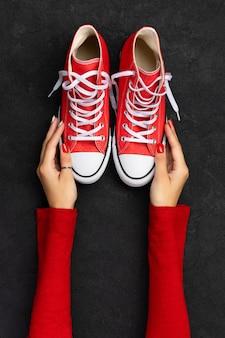Modèle avec des chaussures d'été sur fond noir. plat laïque vue de dessus baskets rouges avec espace de copie. concept de vente shopping de mode
