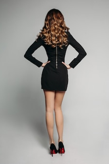 Modèle avec des cheveux ondulés brillants dans une mini robe noire et des talons hauts avec les mains à la taille.