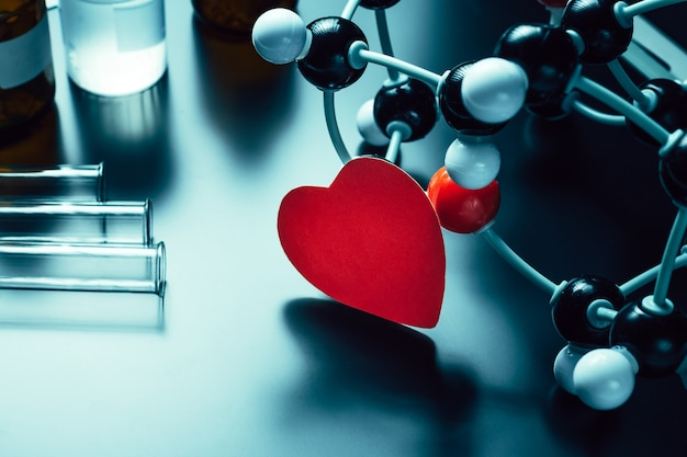 Modèle de coeur et de structure moléculaire en papier rouge sur fond noir. concept de chimie de l'amour