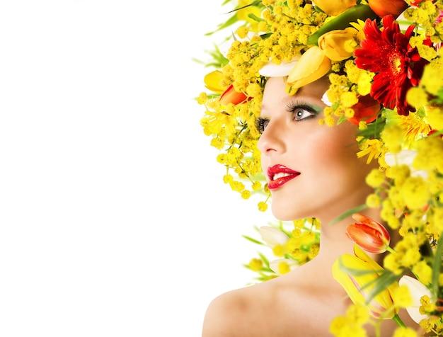 Modèle avec coiffure avec fleurs et maquillage