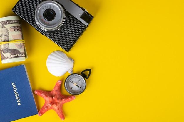 Modèle de conception de bannière de voyage avec appareil photo vintage, passeport, boussole et coquillages sur jaune.