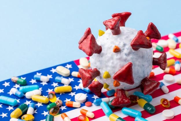 Modèle de coronavirus sur le drapeau des états-unis avec de nombreuses pilules et capsules