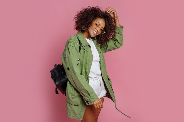 Modèle de course de mélange fascinant dans une veste verte à la mode posant sur fond rose. lunettes de soleil jaunes, sac à dos noir.