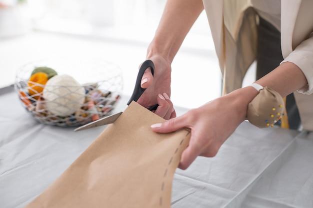 Modèle de couture. gros plan de jeunes mains féminines à l'aide de ciseaux lors de la préparation du modèle