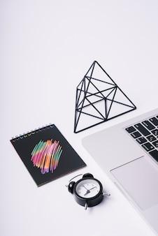 Modèle de couverture de bloc-notes sur le bureau avec ordinateur portable