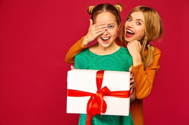 Modèle couvrant les yeux de son amie et lui donnant un grand coffret cadeau