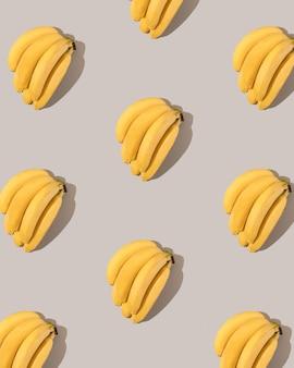 Modèle créatif avec des bananes jaunes sur fond gris. vue à plat.