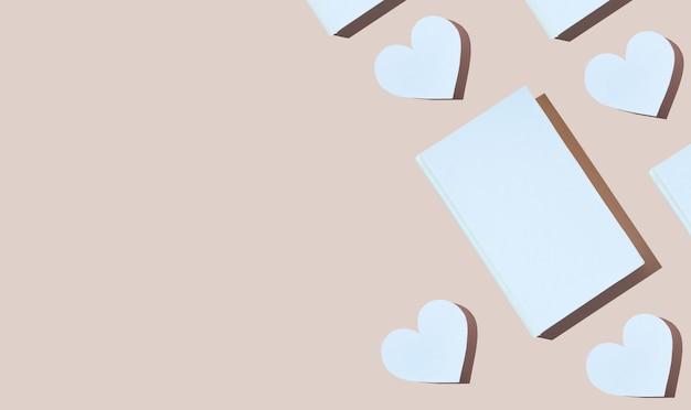 Modèle créatif de coeur de papier mignon et livre de couverture blanc sur fond rose. photo moderne. concept journée nationale des amoureux du livre. joyeuses fêtes. romantique, histoire d'amour. espace de copie