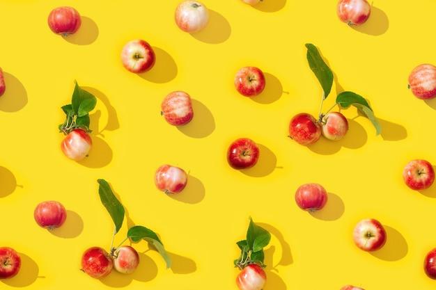 Modèle créatif sans couture de petites pommes rouges et feuilles vertes avec des ombres sombres.