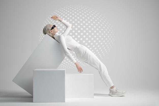 Modèle dans des verres futuristes allongé sur des cubes