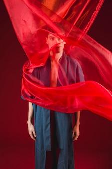 Modèle debout et posant avec un drap rouge