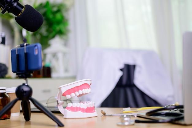 Modèle de dents et équipement pour dentiste travaillant en ligne à la maison. enregistrement vidéo de blog dentisterie.