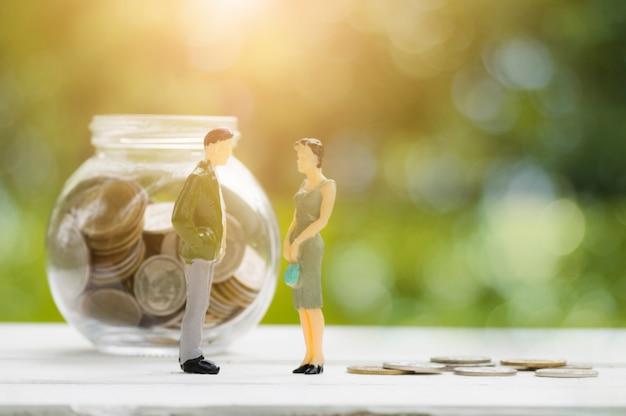 Modèle de deux hommes d'affaires parle de la finance sur le pot d'économiser de l'argent