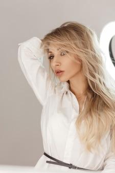 Modèle élégant de belle jeune femme en chemise blanche posant