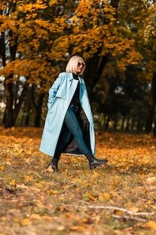 Modèle élégant et élégant de femme blonde en manteau bleu à la mode se promène dans un parc d'automne incroyable avec un feuillage doré brillant