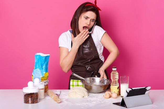 Le modèle émotionnel surpris impressionné pose isolé sur le mur rose, portant un tablier marron et un t-shirt blanc, parlant sur son téléphone portable, l'air choqué par les nouvelles, cuisinant la pâte. concept de cuisson.