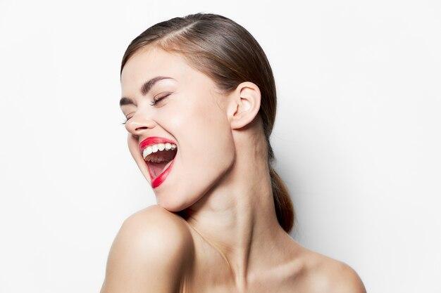 Modèle épaules nues plus amusant yeux fermés lèvres rouges studio maquillage lumineux close-up