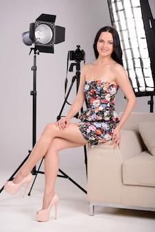 Le modèle est assis dans un studio photo et sourit.