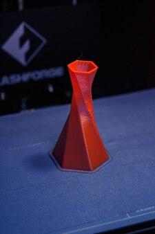 Le modèle est imprimé sur l'imprimante 3d à proximité. imprimante 3d imprimant un objet de couleur rouge sur la base d'un gros plan de fond bleu et noir. technologie d'impression 3d moderne