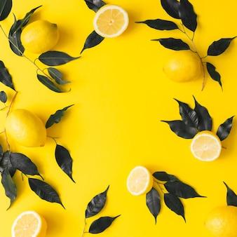 Modèle d'été créatif fait de citrons et de feuilles noires sur fond jaune. concept minimal de fruits. mise à plat.