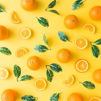 Modèle d'été créatif fait d'oranges et de feuilles vertes sur fond jaune pastel. concept minimal de fruits. mise à plat.