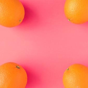Modèle d'été créatif fait d'oranges sur fond rose vif. concept minimal de fruits.