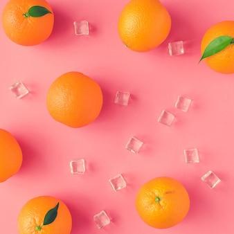 Modèle d'été créatif fait d'oranges et de glaçons sur fond rose vif. concept minimal de fruits.